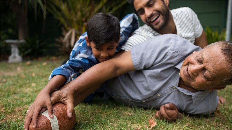 father and son, multigenerational, Indian family, South Asian family, grandpa and grandson, Thanksgiving, football, backyard, outdoor activities, games, family fun