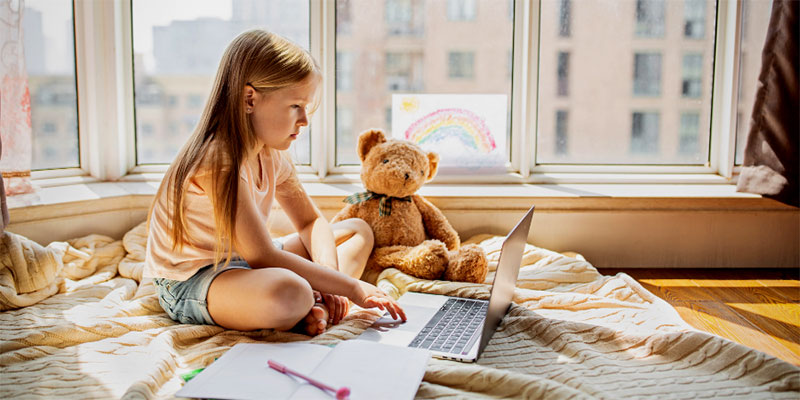 A child sitting isolated on her bed with her teddy bear working on homework.