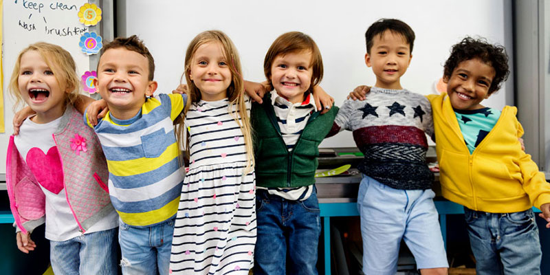 A group of kindergarteners smiling and posing for the camera with their arms around each other's shoulders.