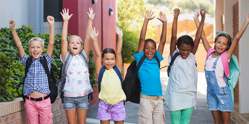 A group of children standing outside wearing backpacks with their arms raised up and smiling