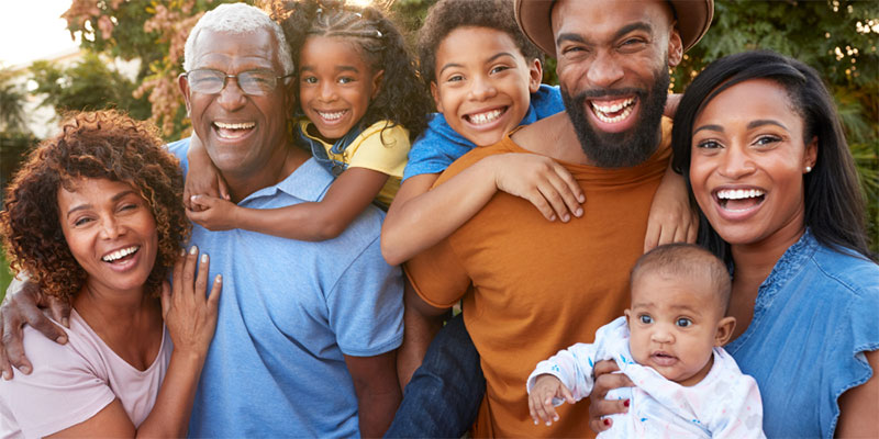 A multi-generational black family poses together smiling.