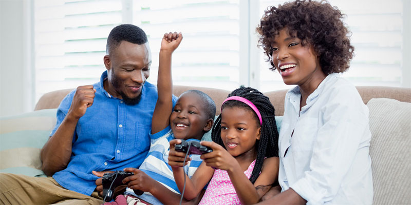 A family of fours sits on the sofa playing video games together.