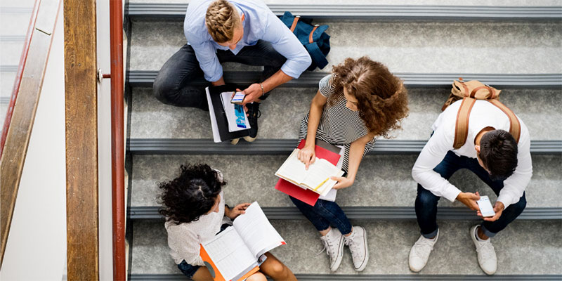 A group of high school students sitting on the stairs and looking at their homework.