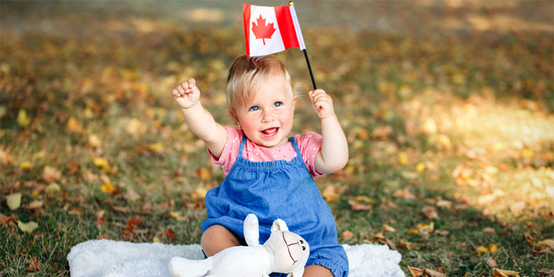 A baby sits on a blanket in the park waving a small Canadian flag