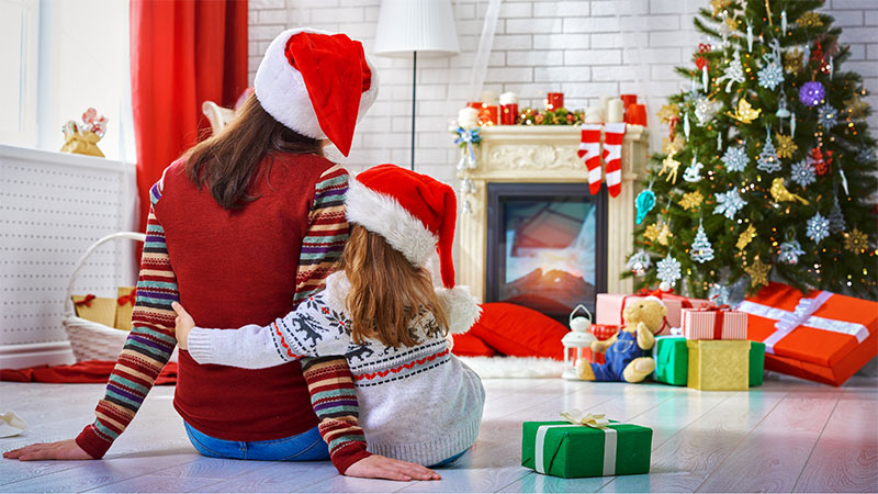A mother and daughter in Santa hats comfort each other while looking at their Christmas tree