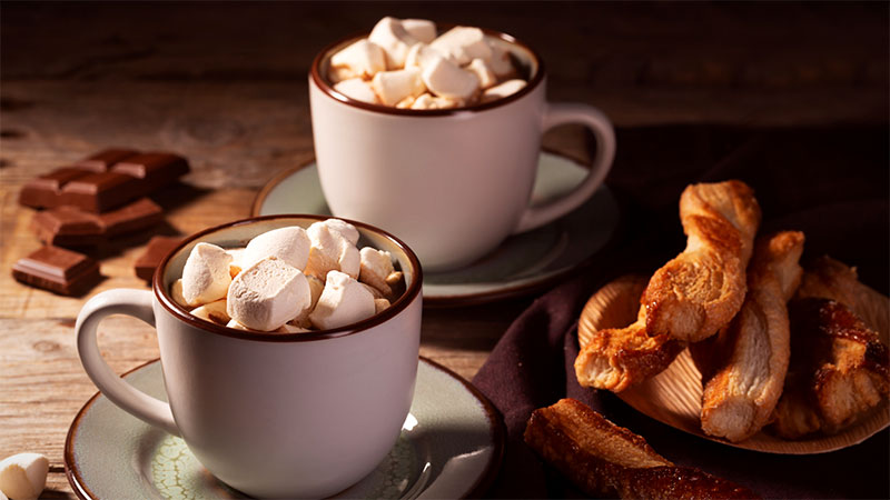 two mugs of hot chocolate topped with marshmallows beside chocolate squares and twisted pastries