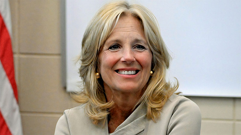 Dr. Jill Biden, seated and smiling in a classroom, will be the First Lady of President-Elect Joe Biden after he is sworn in.