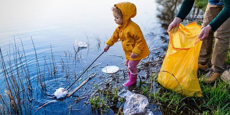 A young girl in a yellow raincoat uses a grabber to pick trash out of a pond while her parent holds open a trashbag.