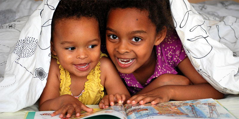 Two African American kids smiling and reading a picture book under a blanket.
