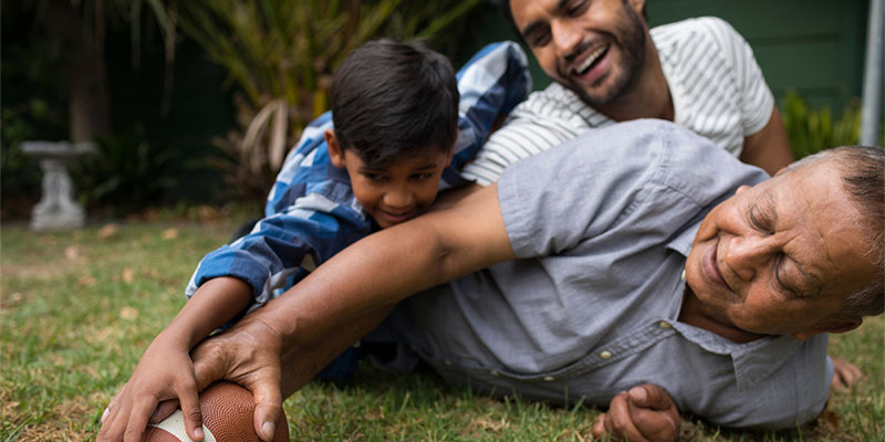 A South Asian son, father, and grandfather play football in their backyard.