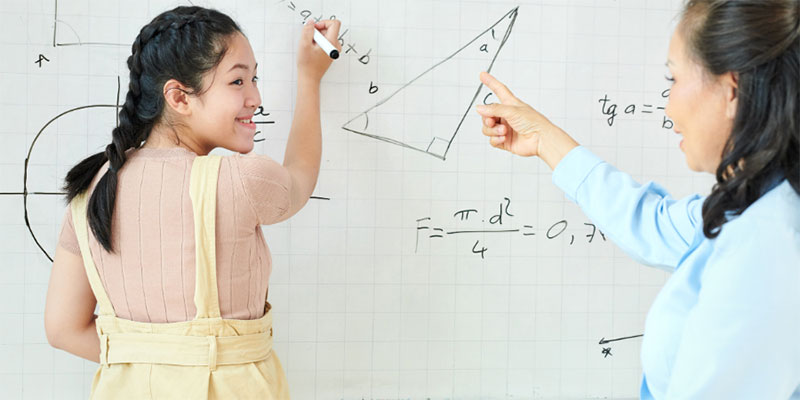 A girl doing math problems on a white board while another girl watches.