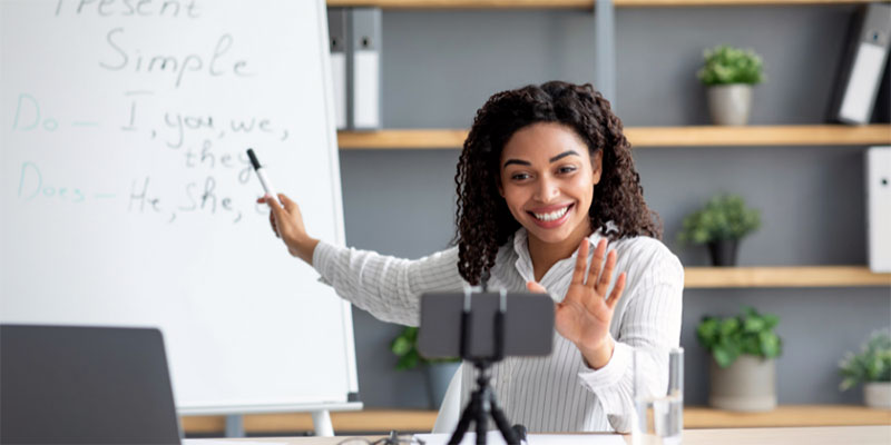 An enthusiastic teacher points to a lesson while teaching an online class.