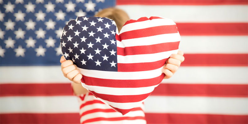 A child holds a heart shaped pillow with an American flag design at the camera while standing in front of an American flag backdrop.