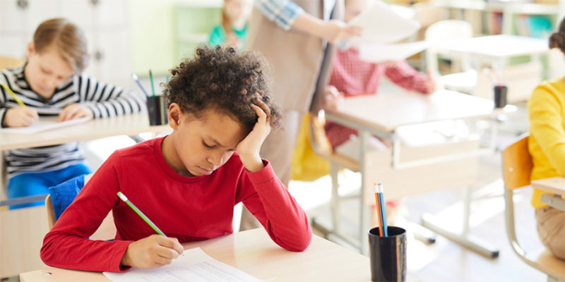 A child sitting in class at their desk and struggling with work