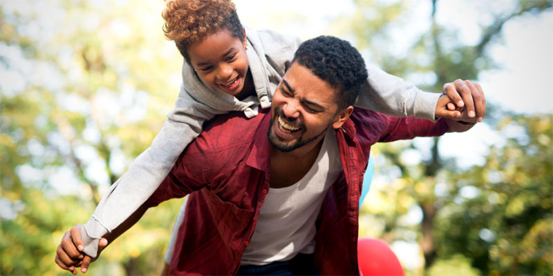 A father picks up his daughter while they both laugh and play in the park.