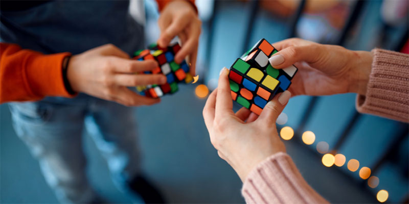 A child and an adult try to solve Rubix cubes.