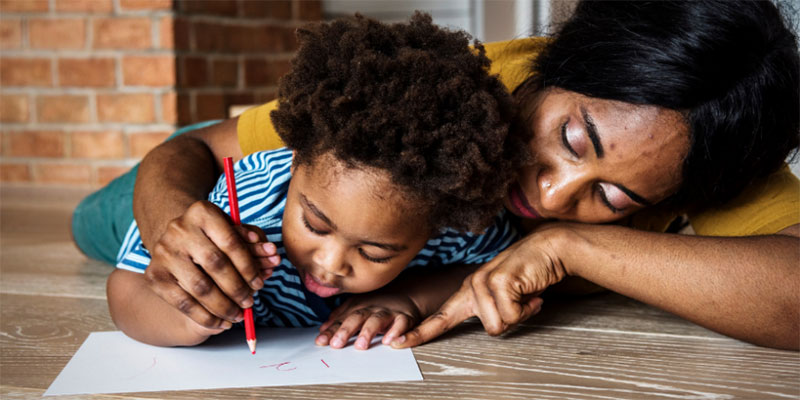A mother holds a pencil with her child and teaches them to write.