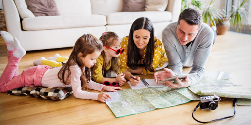 A family gathers on the floor looking over a large map to plan their vacation