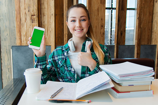 Girl Student using Cell phone and studying