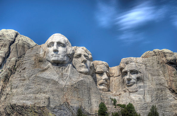 Photo of the four massive heads sculpted into Mount Rushmore look out under a blue sky.