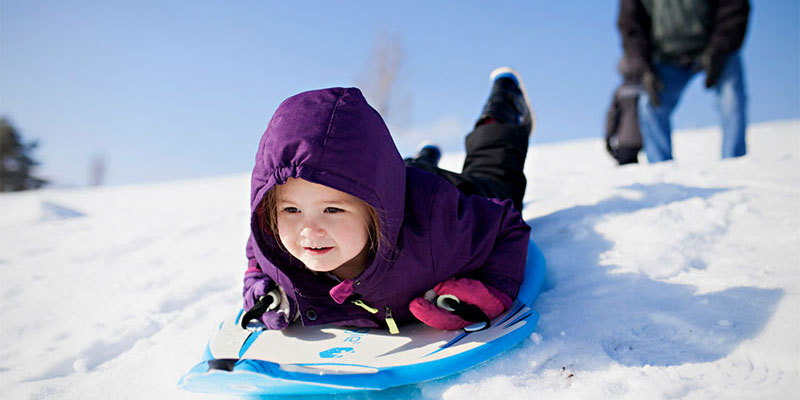 A young girl on a sled sliding downhill while her father watches