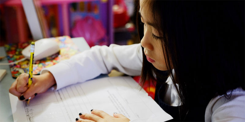 An Asian-American girl holds a pencil and works on homework in her room.