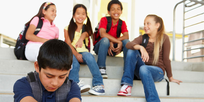 A boy sitting alone and isolated while a group of friends looks at him and laughs.
