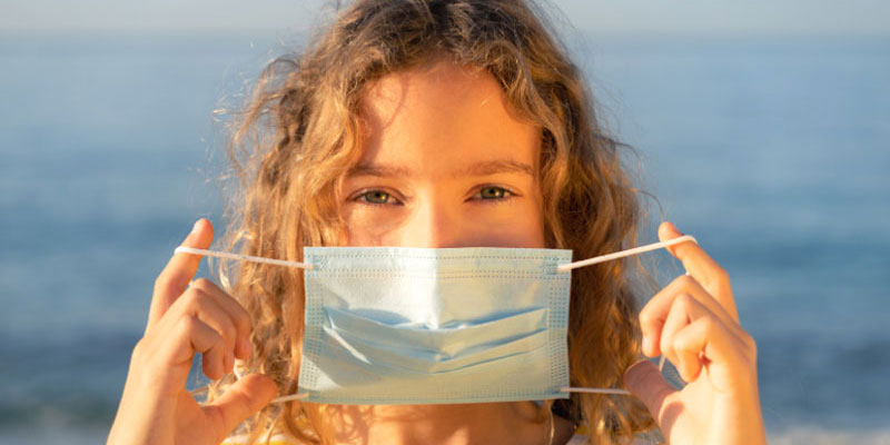A girl holding a medical mask up to her face while on the beach.