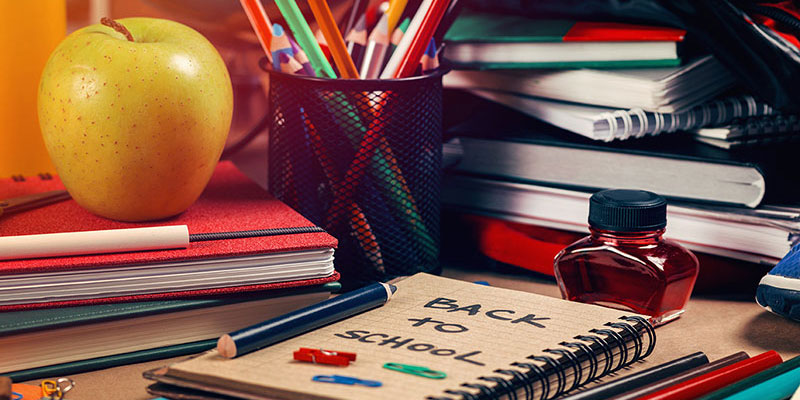 A desk covered in books and papers, school supplies, and an apple.