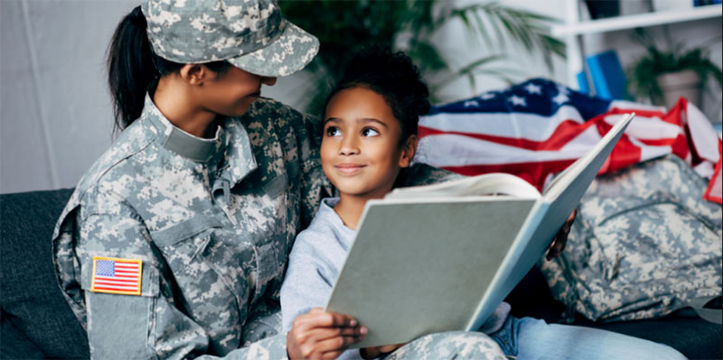 A female veteran sits with her daughter on a sofa reading a book together