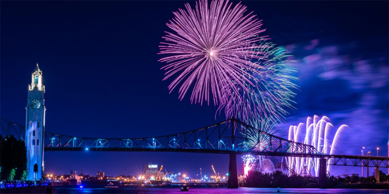 The nighttime sky filled with fireworks over a bridge