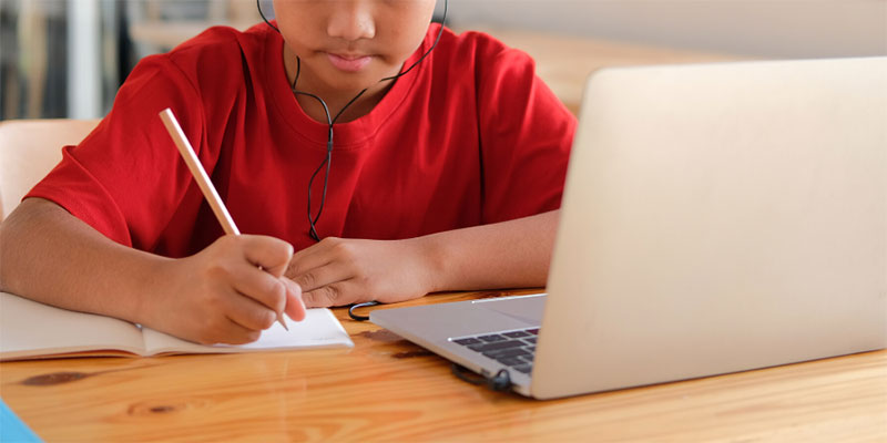 A boy with headphones in taking notes and looking at his laptop.