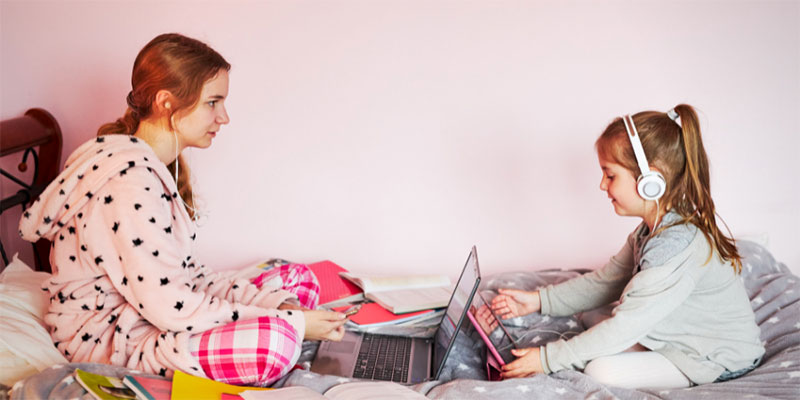 An older sister with a laptop and a younger sister with a tablet sit on a bed wearing headphones and pajamas.