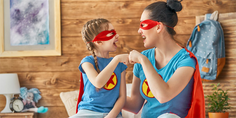 A mother and a daughter dressed up like superheroes